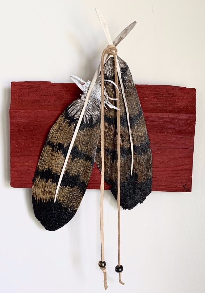 Two feathers connected with deer hide mounted on a a piece of red reclaimed barn wood
