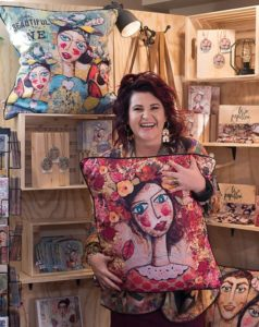 Photograph of Charlene du Toit in front of a store display of her artwork. Charlene is viewed from the knees up. She is wearing a multi-coloured blazer and is holding a decorative pillow with an image of her artwork printed on it. Charlene has red and black hair, is a white woman, is wearing large u shaped earrings and has a large smiles.