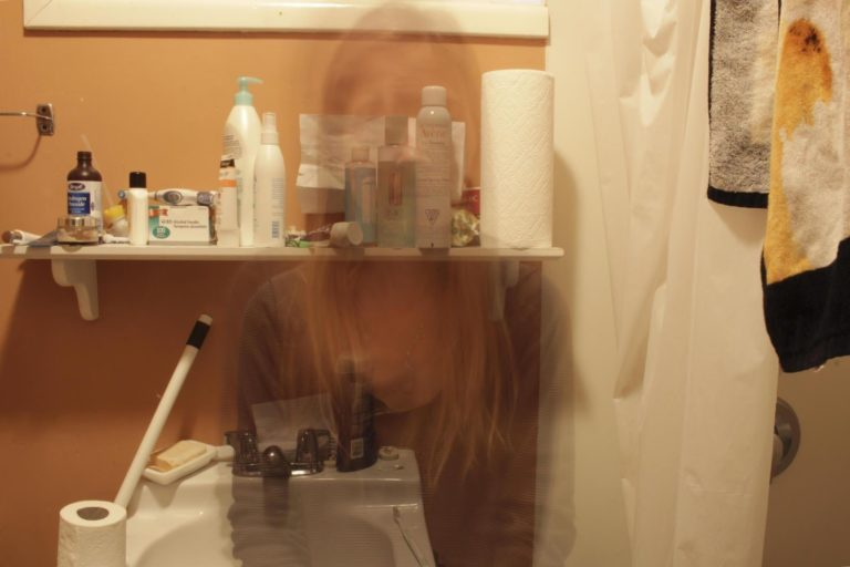 image of a bathroom full of chemicals with the ghost image of a woman