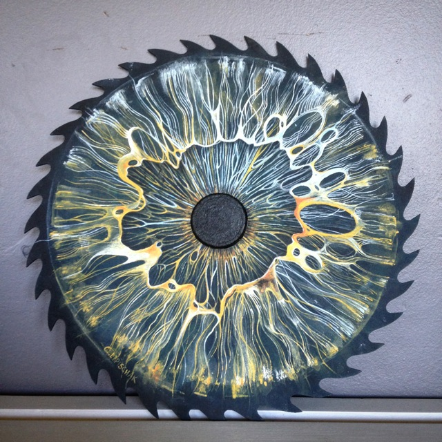 painting of an eye on a metal saw blade