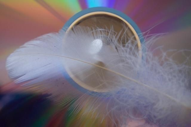 white feather in front of a blue circle with glass in it. the background is a rainbow