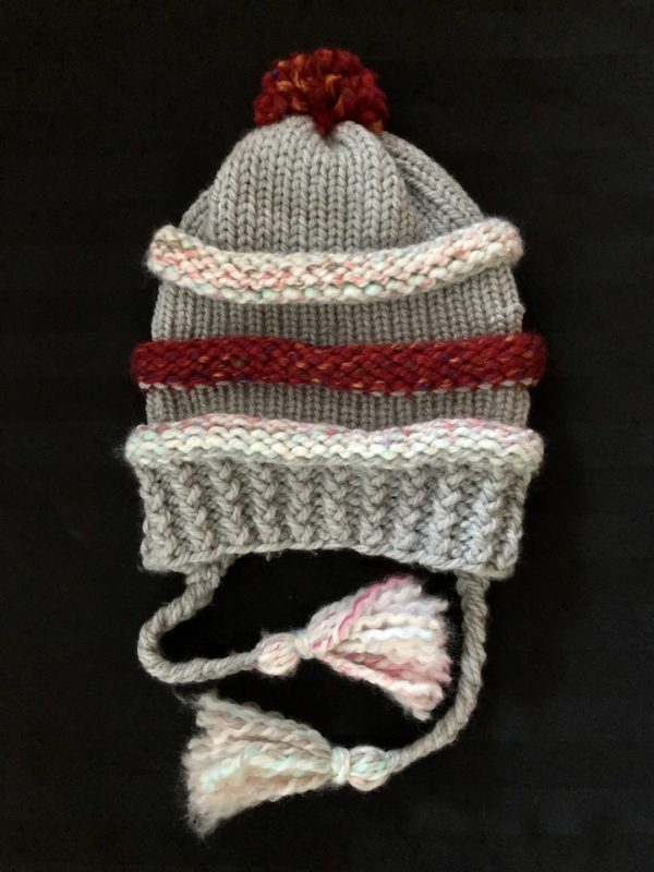 Image of a slouchy red, grey and light pastel knit hat