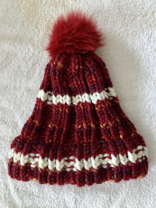 Image of a multi hued red and white knit hat