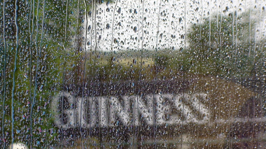 Photograph of a reflective surface with water droplets and rain running down the surface. In the reflections a Guinness sign can be viewed as well as some unidentified greenery