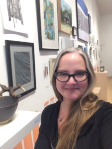 head shot of Dana Kletke. Dana is a Caucasian woman with long straight white and blind hair. She is wearing a black top, a necklace and black rimmed glasses. Dana is standing in front of a white wall covered in artwork