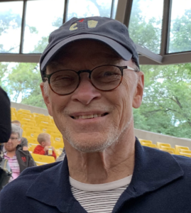 Head shot of Ted Howorth. Ted is a Caucasian male and he is wearing a dark blue baseball cap, a dark blue collared shirt and a white and black striped t-shirt underneath. Ted has a big smile and is wearing glasses