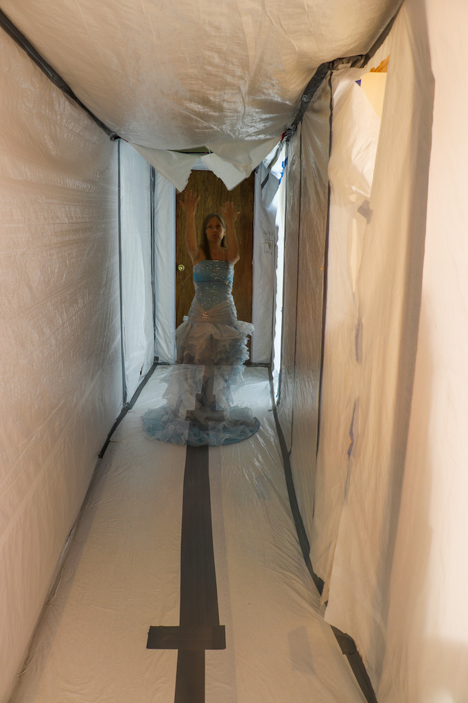 Photograph of a hallway covered in white plastic with grey duct tape. At the end of the hall is a brown wooden door. Superimposed on the image through long exposure is a see-through image of Marie LeBlanc. Marie is a thin white woman with long straight brown hair. Marie is wearing a fancy blue strapless dress with lots of frills on the bottom. Marie is walking down the hall with her arms above her.