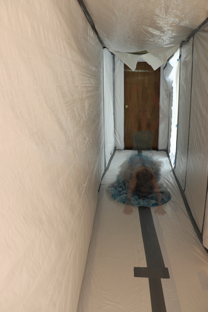 Photograph of a hallway covered in white plastic with grey duct tape. At the end of the hall is a brown wooden door. Superimposed in long exposure on the image are two see-through images of Marie LeBlanc. Marie is a thin white woman with long straight brown hair. Marie is wearing a fancy blue strapless dress with lots of frills on the bottom. Both images of Marie are kneeling. One is looking up with her arms in the air and the other has her head down and arms on the floor stretched out.