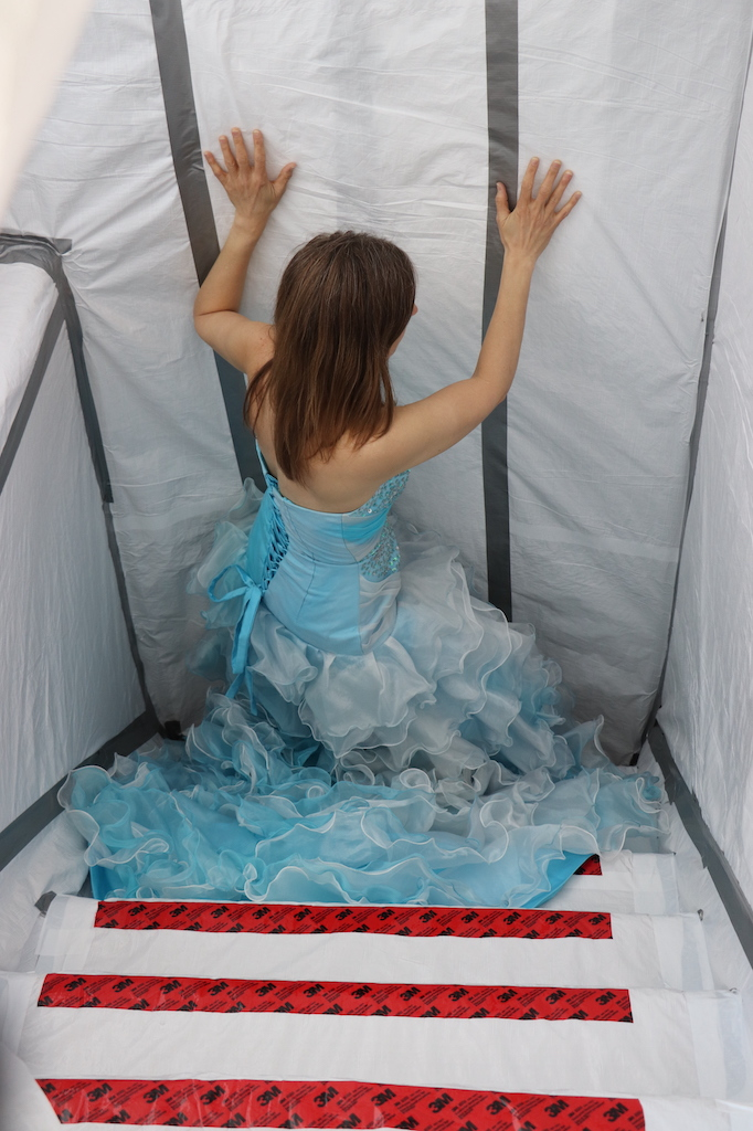 Photograph of a staircase that is blocked with white plastic and duct tape. On the steps is red tape which defines the end of the steps. Marie LeBlanc stands in front of the blocked staircase and is viewed from behind with her arms up and touching the blocked area. Marie is a thin white woman with long straight brown hair wearing a fancy blue strapless dress with lots of frills on the bottom.