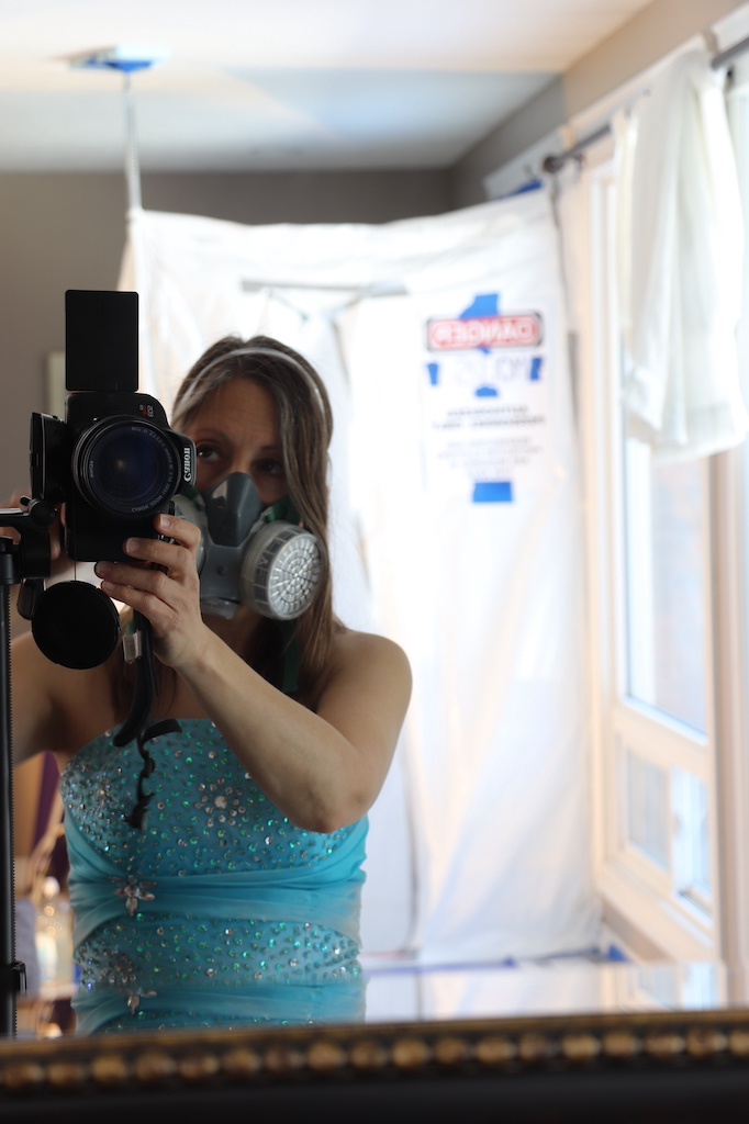 """Photograph of Marie LeBlanc from the waist up. Marie is a thin white woman with long brown hair. She is wearing a heavy-duty respirator and a sparkly strapless blue dress. Marie is looking through the lens of a high-end Canon camera. In the background you can see a blurry image of white plastic with a sign that says """"Danger, MOLD"""". Besides this on the right is a large window with sunlight coming through."""