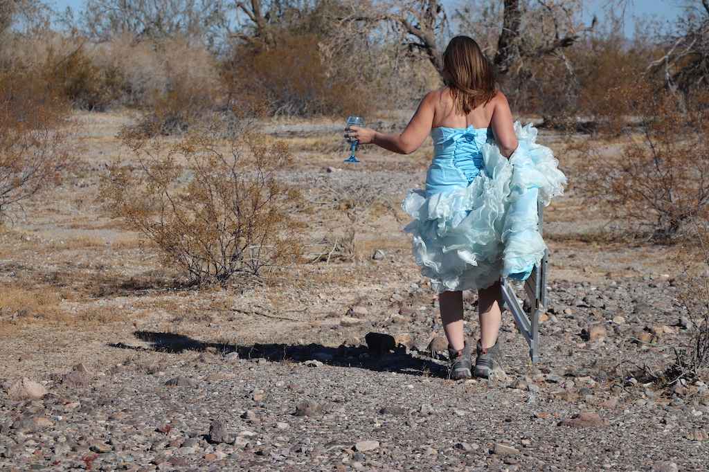 Photograph of Marie LeBlanc standing with her back to the viewer, in a rocky outdoor area with scrub bushes and a tree with no leaves. Marie is a thin white woman with long straight brown hair wearing a fancy blue strapless dress with lots of frills on the bottom and work boots. She is holding a clear blue wine glass with water in her left hand and a folding table in her other hand.