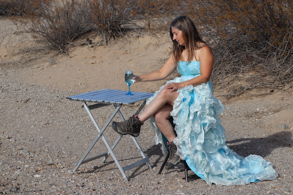 Photograph of Marie LeBlanc sitting on a stool next to a foldout table with a blue clear wine glass with water on it. Marie is a thin white woman with long straight brown hair wearing a fancy blue strapless dress with lots of frills on the bottom and work boots. Marie is sitting outdoors in a rocky and sandy area with scrub bushes behind her.