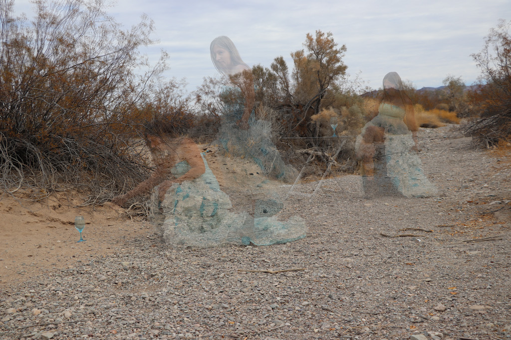 Photograph composed of multiple images superimposed. The background is an outdoor rocky and sandy area with scrub bushes. There are three see through images of Marie LeBlanc, a thin white woman with long straight brown hair wearing a fancy blue strapless dress with lots of frills on the bottom and work boots. On the right side of the image, she is sitting next to a foldout table with a clear blue wine glass with water on it. In the middle is an image of Marie walking and looking towards the camara. The last image of Marie on the left is kneeling down and reaching towards a clear blue wine glass with water in it.