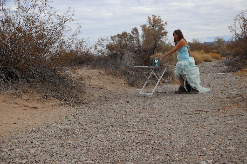 Photograph of Marie LeBlanc, a thin white woman with long straight brown hair wearing a fancy blue strapless dress with lots of frills on the bottom and work boots. Marie is in a rocky and sandy outdoor area with scrub bushes. Marie is standing and reaching for a clear blue wine glass with water in it which is sitting on a foldout table.