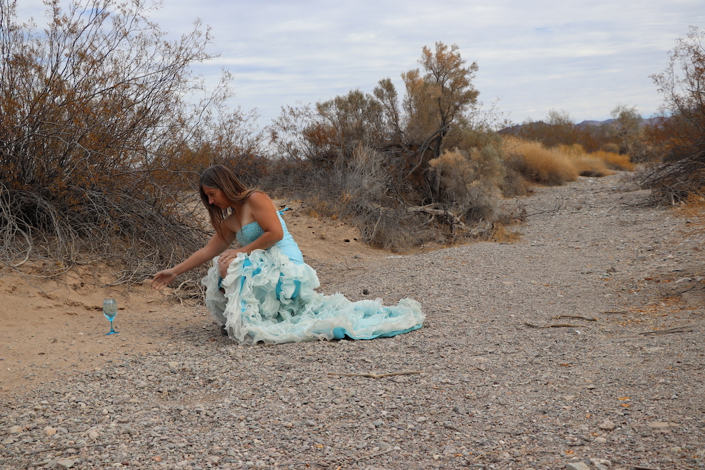 Photograph of Marie LeBlanc, a thin white woman with long straight brown hair wearing a fancy blue strapless dress with lots of frills on the bottom and work boots. Marie is in a rocky and sandy outdoor area with scrub bushes. Marie is kneeling down and reaching out for a clear blue wine glass filled with water that is placed on the ground.