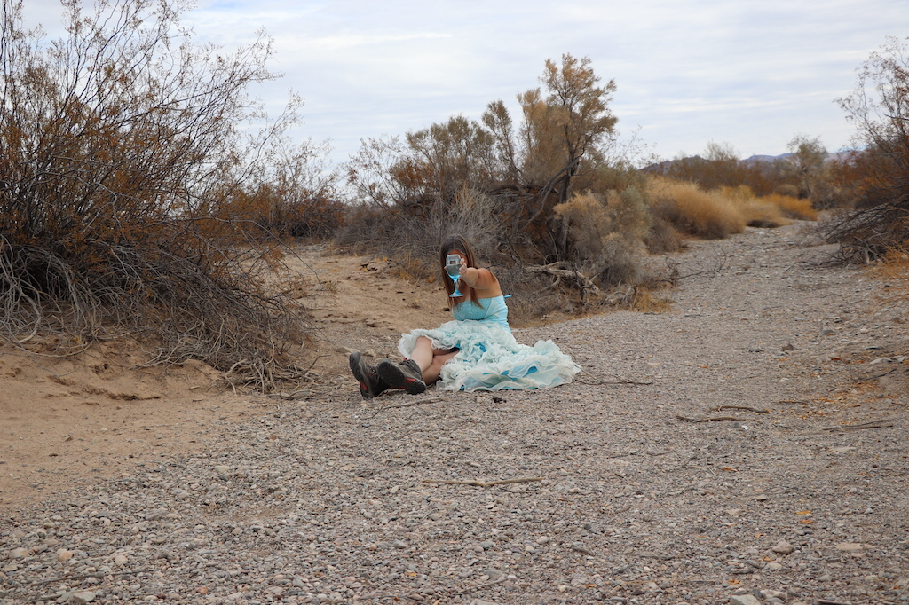 Photograph of Marie LeBlanc, a thin white woman with long straight brown hair wearing a fancy blue strapless dress with lots of frills on the bottom and work boots. Marie is in a rocky and sandy outdoor area with scrub bushes. Marie is sitting on the ground with her legs stretched and crossed in front of her. Marie is holding up a clear blue wine glass with water in it so that it blocks her face.