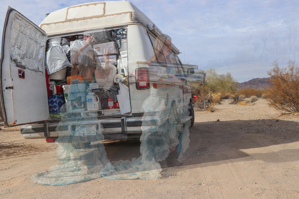 Photograph of the back of Marie LeBlanc's van. The van is all white and the back entrance is opened. Inside the van it is packed all the way to the ceiling with different provisions. The van is parked in a sandy outdoor area with scrub bushes. There are two see-through images of Marie in the photograph. Marie LeBlanc is a thin white woman with long straight brown hair wearing a fancy blue strapless dress with lots of frills on the bottom and work boots. The first image is Marie from behind as she searches through the van. The second image to the right of the first shows Marie facing the viewer and walking away holding her solar cooker, a long metallic device.