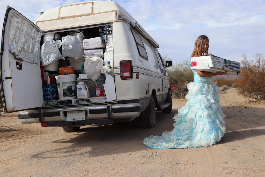 Photograph of the back of Marie LeBlanc's van. The van is all white and the back entrance is opened. Inside the van it is packed all the way to the ceiling with different provisions. The van is parked in a sandy outdoor area with scrub bushes. Marie LeBlanc is also in the image to the right of the van. Marie is a thin white woman with long straight brown hair wearing a fancy blue strapless dress with lots of frills on the bottom and work boots. Marie is facing the viewer and walking away holding her solar cooker and its box.