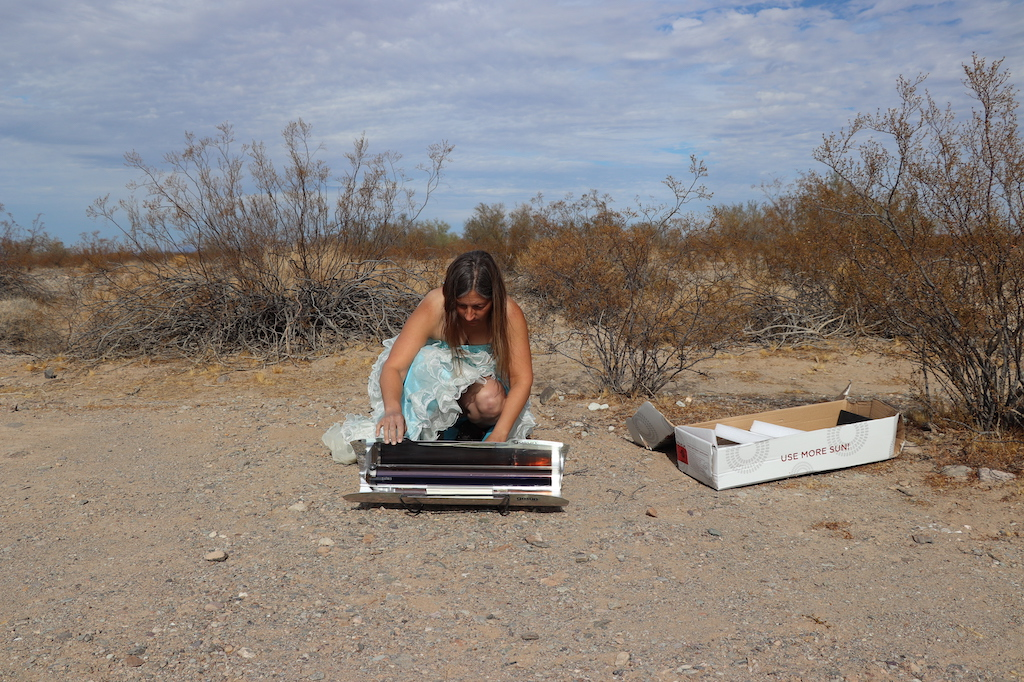 Photograph of Marie LeBlanc in an outdoor and sandy area with scrub bushes behind her. Marie is a thin white woman with long straight brown hair wearing a fancy blue strapless dress with lots of frills on the bottom and work boots. Marie is kneeling on the ground and is opening up the box that her solar cooker is in.