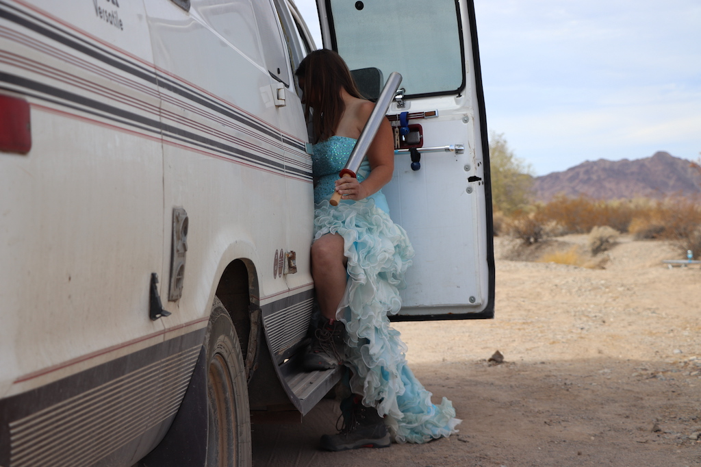 Photograph of Marie LeBlanc standing next to the side of her white van with one foot on the step. Marie is a thin white woman with long straight brown hair wearing a fancy blue strapless dress with lots of frills on the bottom and work boots. She is holding her solar cooker in her right hand which is a long metal tube with a wooden handle. The van is parked in a sandy and rocky outdoor area. Scrub bushes and  mountains can be seen in the distance on the right-hand side of the photograph.