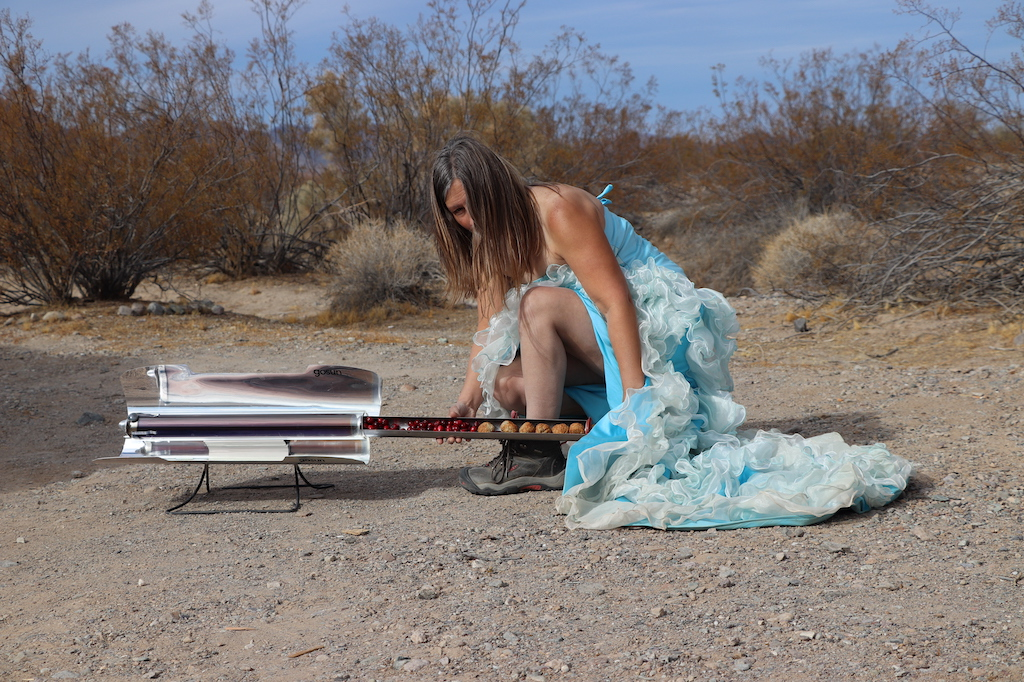 Photograph of Marie LeBlanc, a thin white woman with long straight brown hair. Marie is wearing a blue strapless dress with lots of frills on the bottom. Marie is kneeling down next to her solar cooker which contains berries and round food. Marie is kneeling in a rocky and sandy area with scrub bushes in the background.