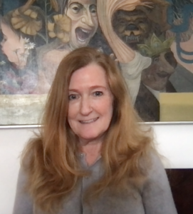 Photograph of Susan Lamberd. Susan is a white woman with long city blond hair. She is wearing a grey sweater and is seated in front of a surrealist painting