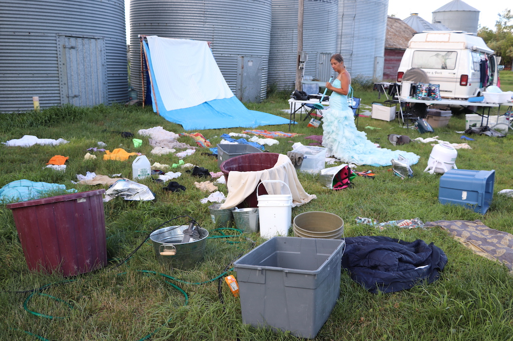 Photograph of Marie LeBlanc doing her laundry in a grassy area in front of four Silo bins. Marie is a thin white woman with long brown hair that is tied up. She is wearing a blue fancy dress with frills on the bottom. She is holding a blue plunger. Pails and buckets full of water and clothes are strewn all over the grass with laundry all over the place and some sheets hanging near the silos. The image illustrates difficulty she has when doing her laundry.