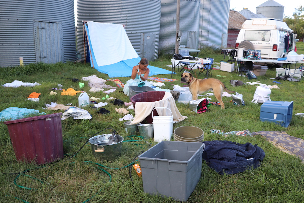 Photograph of LeBlanc doing her laundry. The photograph is of an outdoor area with lots of grass and four metal grain bins. Marie's laundry and pails are strewn all over the grass. Marie is seen using a blue plunger to mix her laundry in a bucket. Marie is a thin white woman with long brown hair that is tied up. Marie is wearing a blue fancy dress with lots of frills on the bottom. There is also friendly brown dog in the photograph next to Marie.