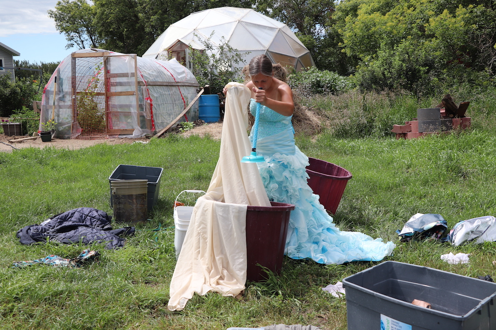 Photograph of Marie LeBlanc doing her laundry. In the background, in a grassy area with lots of trees, a geo dome can be seen in front of a homemade greenhouse. Marie is standing in front of a bucket holding a sheet and a blue plunger as she washes her linen by hand. Marie is a thin white women with long straight brown hair that is tied back and she is wearing a fancy blue dress with frills on the bottom.