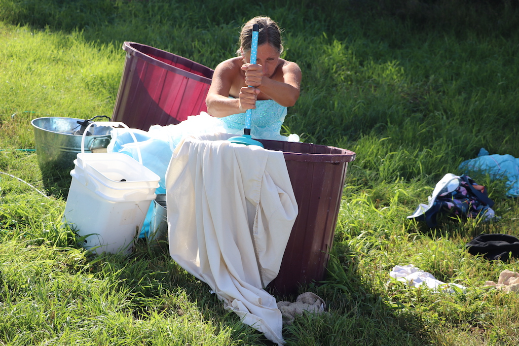 Close-up photograph of Marie LeBlanc as she does her laundry in a grassy field. Marie is a thin white woman with long straight brown hair that is tied back and she is wearing a fancy blue dress with lots of frills on the bottom. Marie is sitting in the grass behind a bucket washing her laundry with a blue plunger. There are other buckets around Marie as well as a water hose.