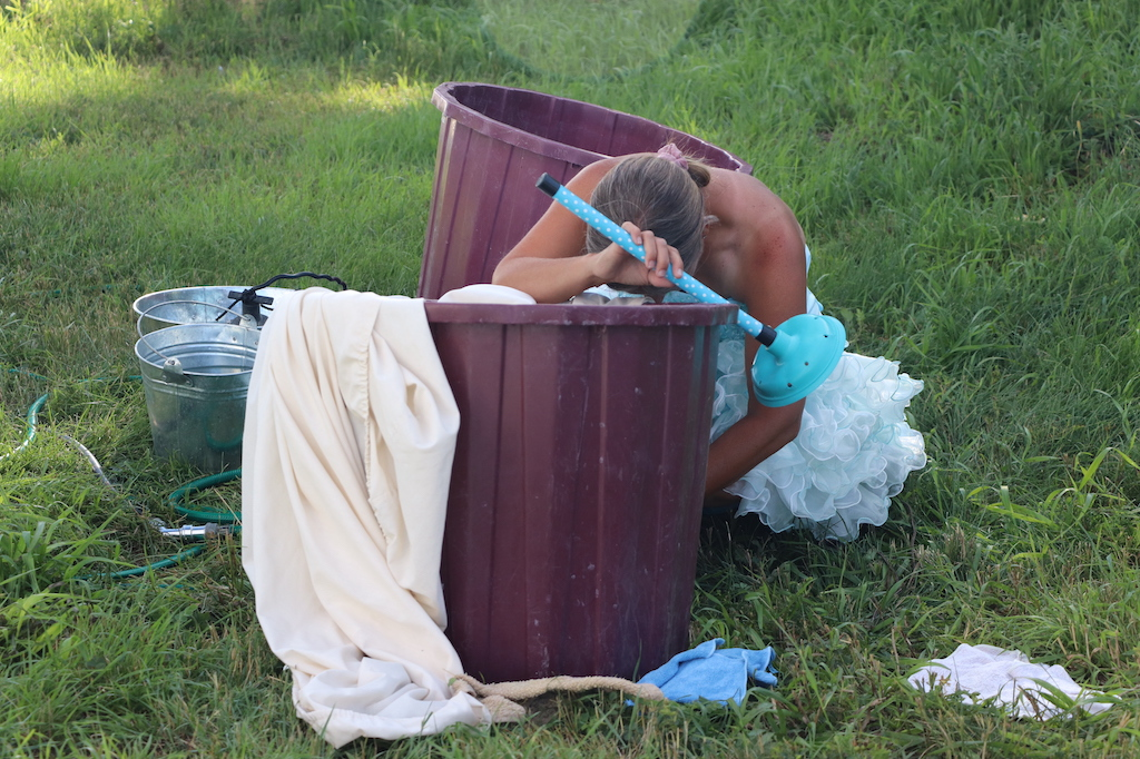 Photograph of Marie LeBlanc doing her laundry in a grassy field. Marie is a thin white woman with long straight brown hair that is tied up and is wearing a blue fancy dress with frills on the bottom. Marie can be seen with her head hanging over the bucket of laundry as though she is exhausted.