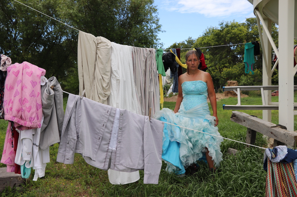 Photograph of Marie LeBlanc standing next to all of her laundry that is drying outdoors. Marie is standing in a grassy area with lots of trees behind her and a blue sky. Marie is a thin white woman with long brown hair that is tied up behind her. Marie is wearing a blue fancy strapless dress with lots of frills at the bottom and work boots. Marie is not smiling and looks very tired and tanned.