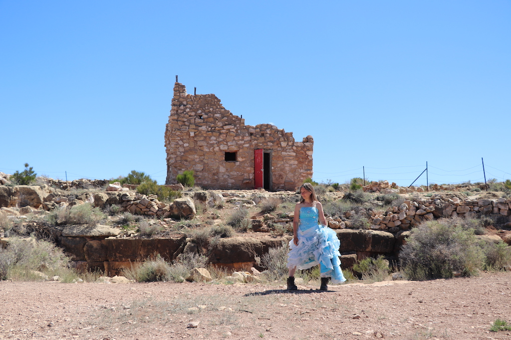 Photograph of Marie LeBlanc standing outside in a rocky area with scrub bushes. The sky is blue and sunny. Behind Marie there is a stone building with no roof, a red door and a small window without glass. The stone building is surrounded by stone rubble. Marie is a thin white woman with long straight brown hair and is wearing a blue strapless dress with lots of frills at the bottom and work boots. She is holding up the train of her dress and looking to the left.