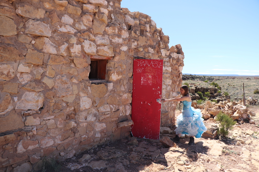 Photograph of Marie LeBlanc reaching for the red door covered with graffiti of a run-down stone building with no roof, a small window with no glass. Marie is a thin white woman with straight long brown hair and is wearing a blue strapless dress with lots of frills at the bottom and work boots. The ground outside the building is covered in rocks and scrub bushes. The sky is blue and sunny.