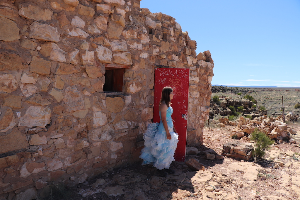 Photograph of Marie LeBlanc standing next to a red door covered with graffiti of a run-down stone building with no roof and a small window with no glass. Marie is a thin white woman with straight long brown hair and is wearing a blue strapless dress with lots of frills at the bottom and work boots. Marie is looking off to the right in the distance. The ground outside the building is covered in rocks and scrub bushes. The sky is blue and sunny.