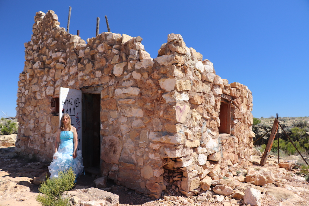 Photograph of Marie LeBlanc leaning against the interior side of a white door covered with graffiti of a run-down stone building with no roof and two small windows with no glass. Marie is a thin white woman with straight long brown hair and is wearing a blue strapless dress with lots of frills at the bottom and work boots. The ground outside the building is covered in rocks and scrub bushes. The sky is blue and sunny.