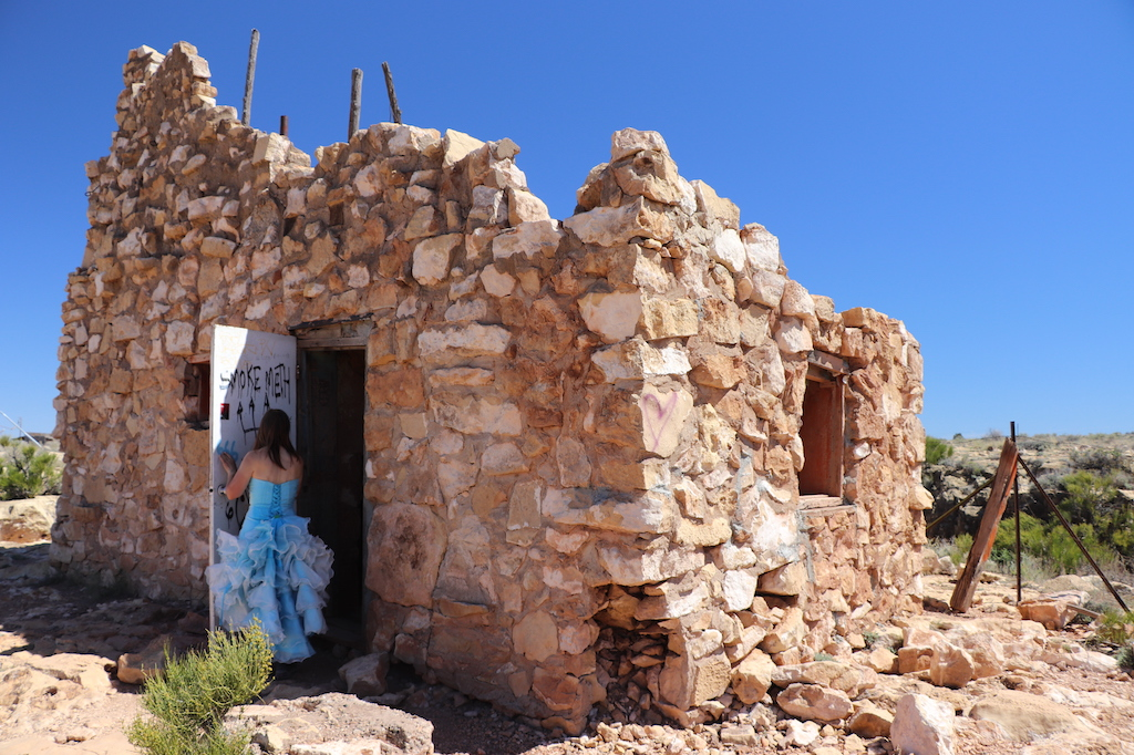 Photograph of Marie LeBlanc touching the interior of a white door covered with graffiti of a run-down stone building with no roof and two small windows with no glass. Marie is a thin white woman with straight long brown hair and is wearing a blue strapless dress with lots of frills at the bottom and work boots. The ground outside the building is covered in rocks and scrub bushes. The sky is blue and sunny.