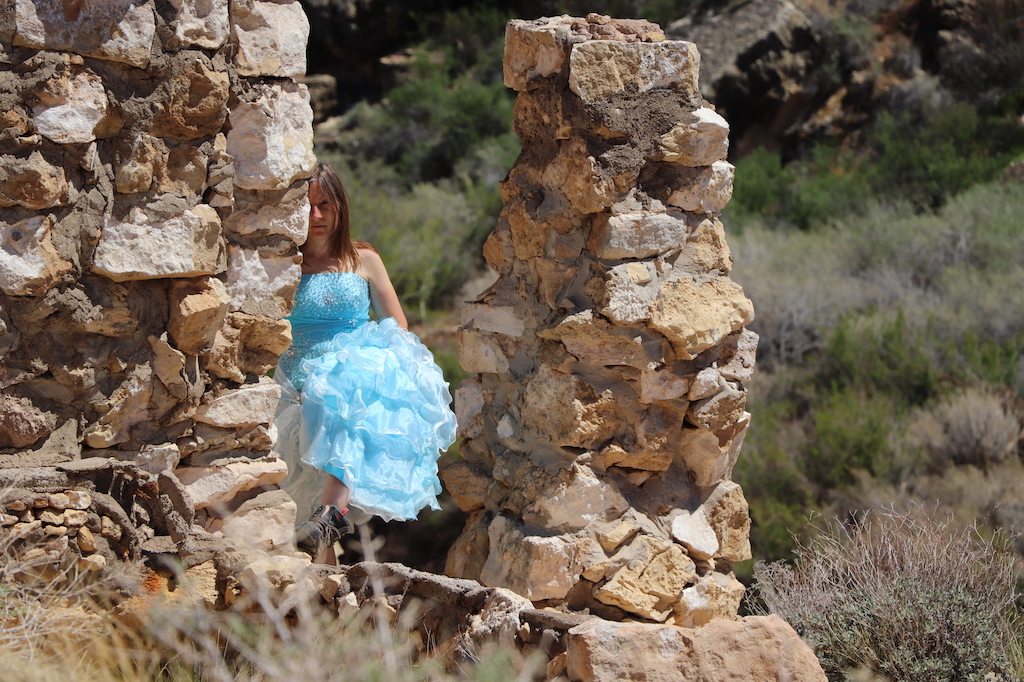 Photograph of Marie LeBlanc standing next to stone rubble. Marie is a thin white woman with straight long brown hair and is wearing a blue strapless dress with lots of frills at the bottom and work boots. Behind the rubble scrub bushes, grass and rocks can be seen.