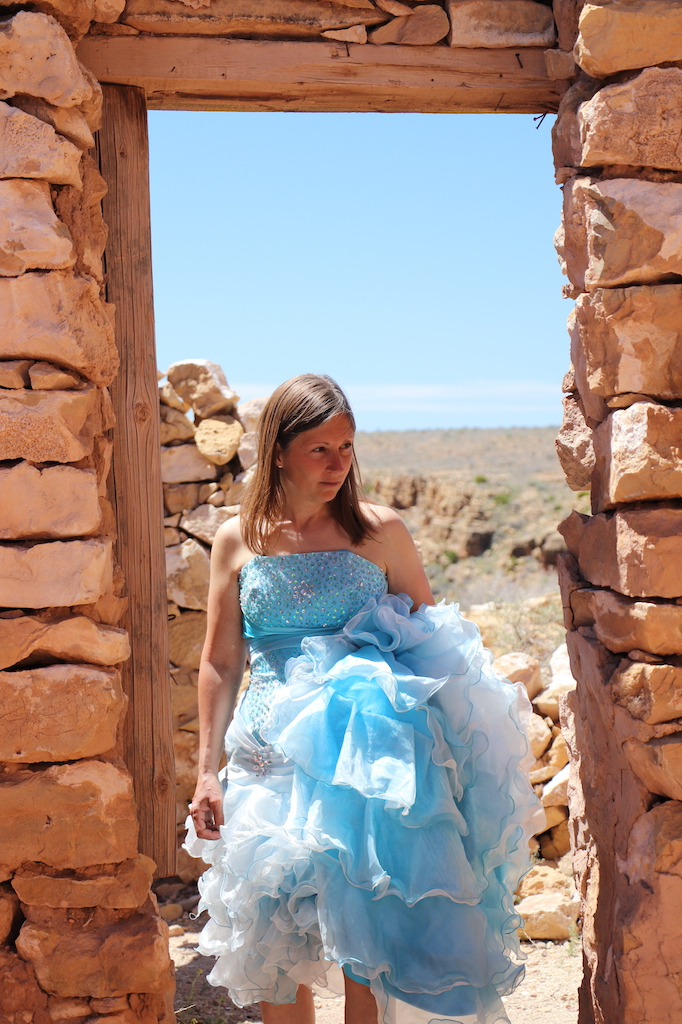 Photograph of Marie LeBlanc standing in the doorway of a rocky building. Marie is a thin white woman with long straight brown hair. Marie wearing a strapless blue dress with lots of frills at the bottom. The viewer is looking through the door to the bright blue sky and rocky terrain behind Marie.