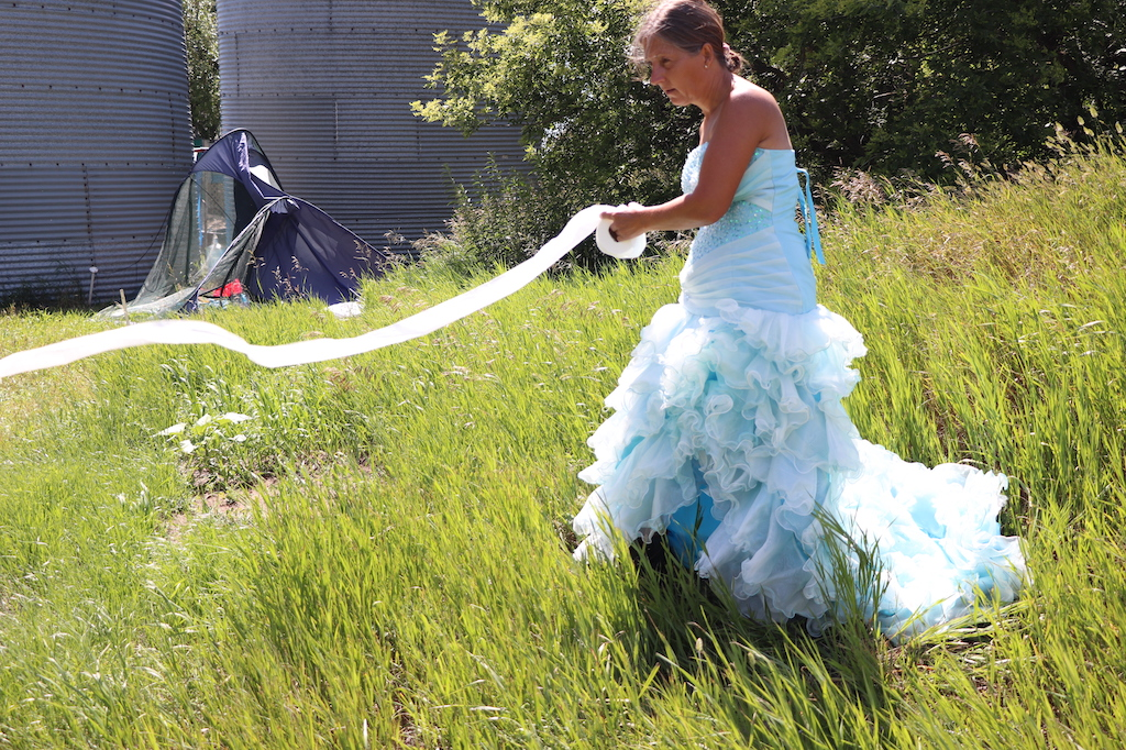 Photograph of Marie LeBlanc standing in a grassy area with trees behind her, a broken tent and two grain silos. Marie is holding a toilet paper roll toilet paper flowing off of it. Marie is a thin white woman with long straight brown hair that is pulled back. Marie is wearing a blue strapless dress with lots of frills on the bottom.