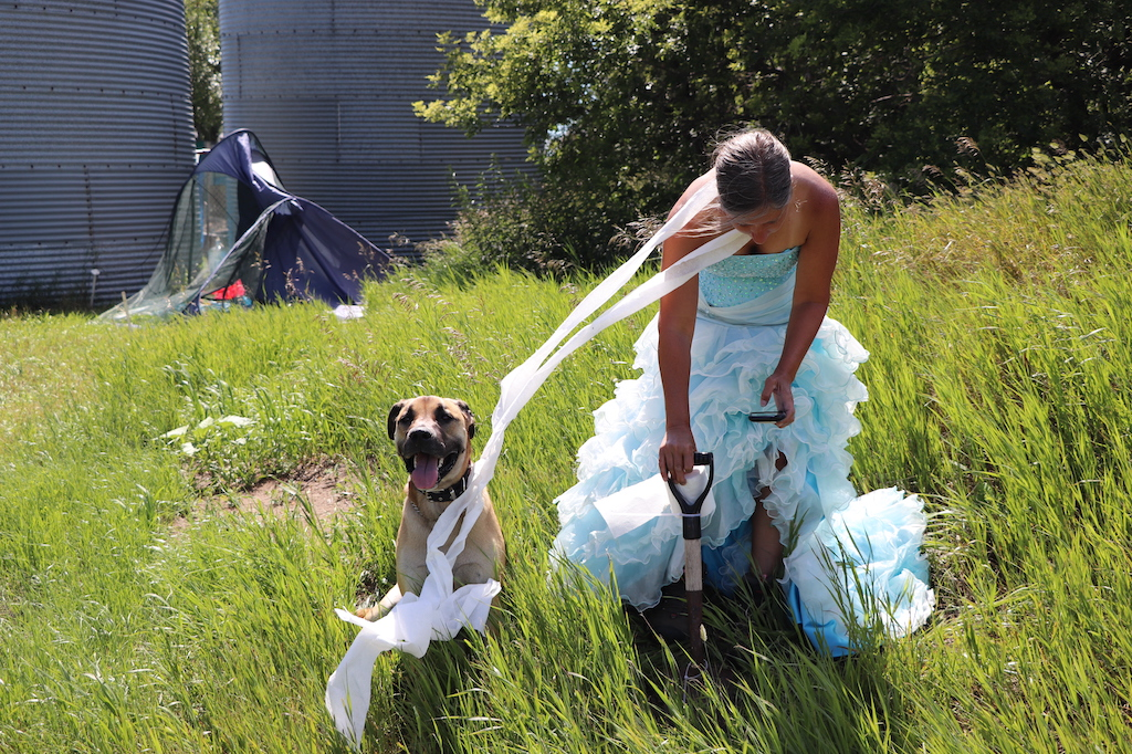 Photograph of Marie LeBlanc standing in a grassy area with trees behind her, a broken tent and two grain silos. Marie is bending over with a shovel and has toilet paper around her neck and flowing in the wind. There is a dog sitting beside her. Marie is a thin white woman with long straight brown hair that is pulled back. Marie is wearing a blue strapless dress with lots of frills on the bottom.