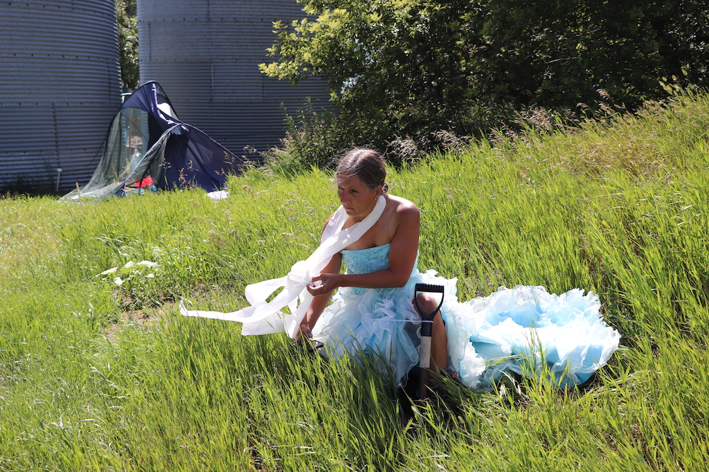 Photograph of Marie LeBlanc sitting in a grassy area with trees behind her, a broken tent and two grain silos. Marie is sitting with a small shovel against her and has toilet paper around her neck and flowing in the wind. Marie is a thin white woman with long straight brown hair that is pulled back. Marie is wearing a blue strapless dress with lots of frills on the bottom.