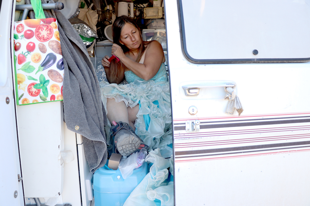 Photograph of Marie LeBlanc sitting in her white van combing her hair. There is one door open in the van, the interior is filled with supplies such as lights, water and tinfoil (to cover supplies that are toxic to her). Marie is a thin white woman with long straight brown hair that is pulled back. Marie is wearing a blue strapless dress with lots of frills on the bottom and work boots.