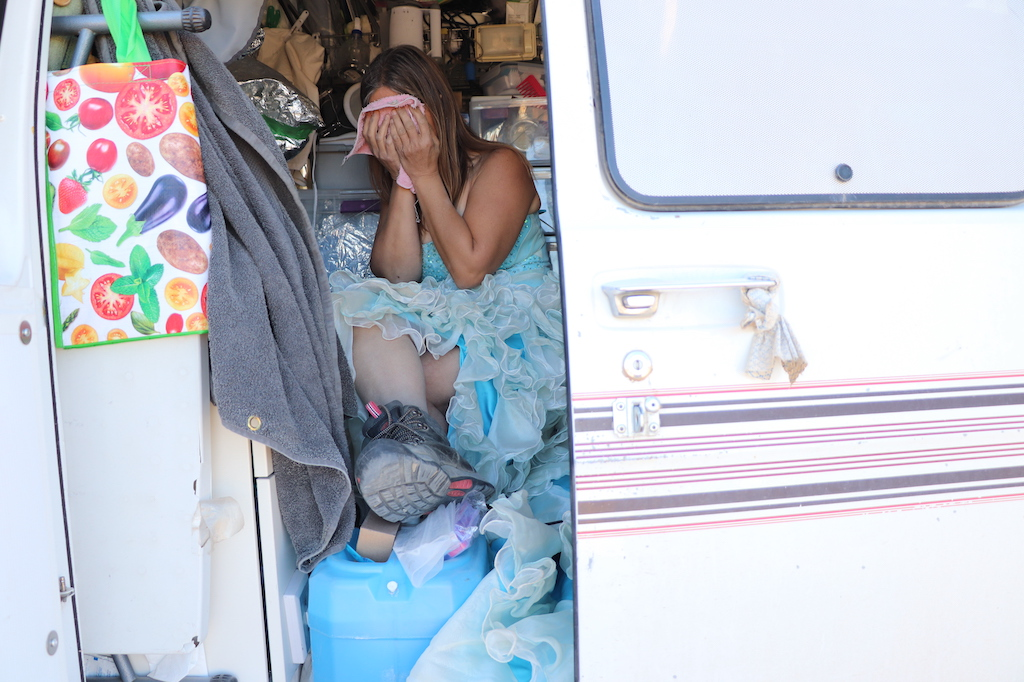 Photograph of Marie LeBlanc sitting in her white van washing her face with a pink cloth. There is one door open in the van, the interior is filled with supplies such as lights, water and tinfoil (to cover supplies that are toxic to her). Marie is a thin white woman with long straight brown hair that is pulled back. Marie is wearing a blue strapless dress with lots of frills on the bottom and work boots.
