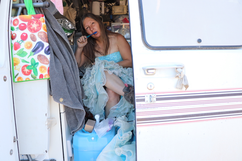 Photograph of Marie LeBlanc sitting in her white van brushing her teeth with a blue toothbrush. There is one door open in the van, the interior is filled with supplies such as lights, water and tinfoil (to cover supplies that are toxic to her). Marie is a thin white woman with long straight brown hair that is pulled back. Marie is wearing a blue strapless dress with lots of frills on the bottom and work boots.