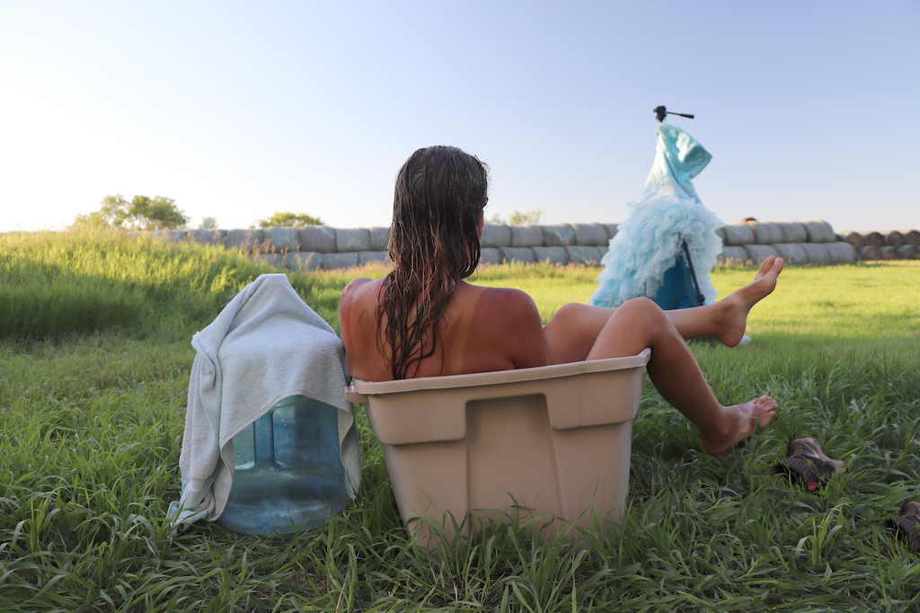 Photograph of Marie LeBlanc taking a bath in a tan coloured plastic container. Marie has her back to us and her legs sticking out over the side of the container. Marie is bathing in a grassy filed with haybales in the distance. Marie's blue strapless dress is hanging on her camera stand. There is a large water bottle with a white towel draped over it. Marie is a white woman with tanned skin and long brown hair that is wet.