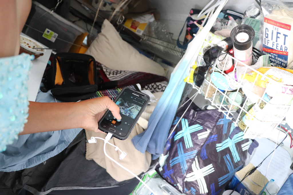 Photograph of Marie LeBlanc's hand holding a cell phone. The photograph is taken inside of Marie's van that is packed with supplies such as food, sunglasses, blankets, and toilet paper. Marie is a white woman with tanned skin.