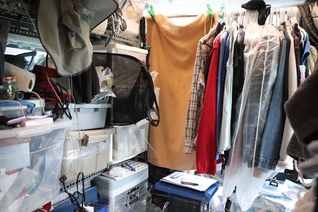 Photograph of the interior of Marie LeBlanc's van. On the left-hand side of the van are metal shelves holding plastic tubs filled with living supplies such as toothbrushes, paper towel, electronic cords, etc. on the right-hand side is a metal bar from which clothing hangs.