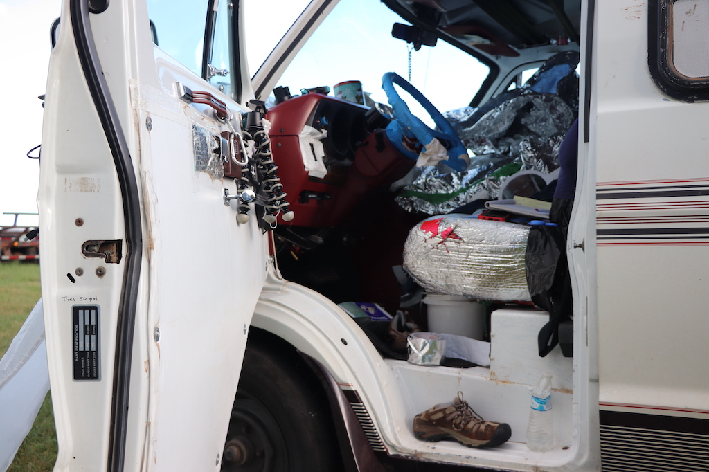 Photograph of Marie's van. The driver's door is open and inside can be seen lots of tinfoil and special foil coverings that protect Marie from the scented fabric of the seat and the steering wheel which Marie has adverse reactions to. The van is packed with supplies such as a hand mirror, a water bottle, a mug, shoes, aluminum tape and such.