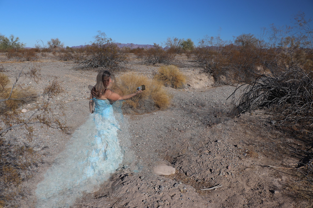 Photograph of Marie LeBlanc standing outside in a rocky and dry area with lots of scrub bushes and low mountains in the distance. There are two images of Marie superimposed in the photograph. One is of Marie from behind as she holds an electronic device (triField meter to measure magnetic, electric and RF). The other image of Marie is facing the viewer as she measures her environment with the triField meter. Both images of Marie are transparent. Marie is a thin white woman with straight long brown hair and is wearing a blue strapless dress with lots of frills at the bottom.